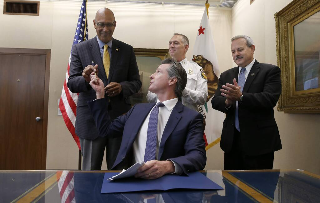 Gov. Gavin Newsom hands Assemblyman Chris Holden, D-Pasadena, left, the pen he used to sign Holden's wildfire bill as Thom Porter, the director for the California Department of Forestry and Fire Protection, center, and Mark Ghilarducci, the director of the California Governor's Office Emergency Services, right, look on in Sacramento, Calif., Friday, July 12, 2019. The bill AB1054, is aimed at stabilizing the state's electric utilities in the face of devastating wildfires caused by their equipment. (AP Photo/Rich Pedroncelli)