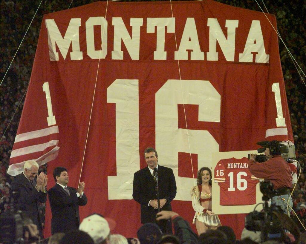 Joe Montana, middle, gets a standing ovation from the crowd as Bill Walsh, left, and Eddie DeBartolo join in during halftime ceremonies retiring the jersey of No. 16.