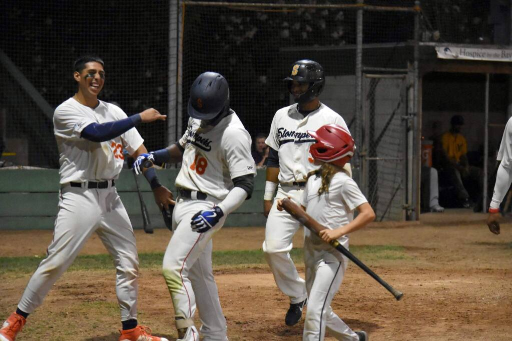 Jacob Barfield (23) congratulates Miles Williams (18) on his 8th-inning grand slam, which scored Barfield, Pedro Barrios (3) and Matt Hibbert as well. The Stompers won, 19-6 over the Vallejo Admirals. (James W. Toy III / Stompers Baseball)
