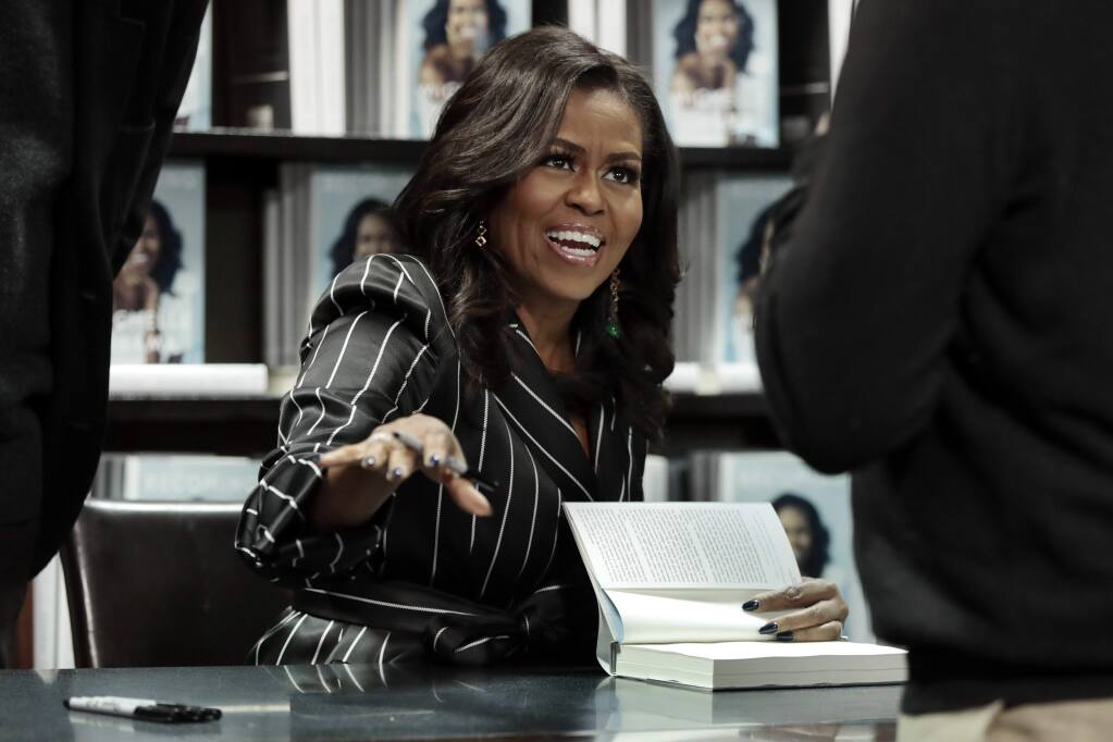 FILE - In this Nov. 30, 2018, file photo, Former First Lady Michelle Obama signs books during an appearance for her book, 'Becoming,' in New York. (AP Photo/Richard Drew, File)