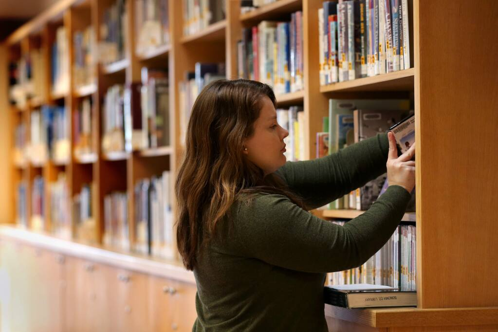 Megan Jones, curator of the Sonoma County Wine Library, puts away a book on the shelf at the library in Healdsburg on Tuesday, March 19, 2019. (BETH SCHLANKER/ The Press Democrat)