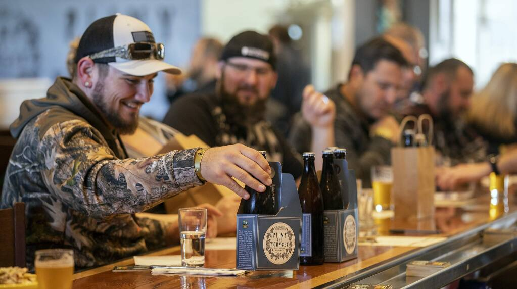 Logan Jackson of San Jose lines up his take home bottles Pliny the Younger triple IPA for a photo at the Russian River Brewery in Windsor. (photo by John Burgess/The Press Democrat)