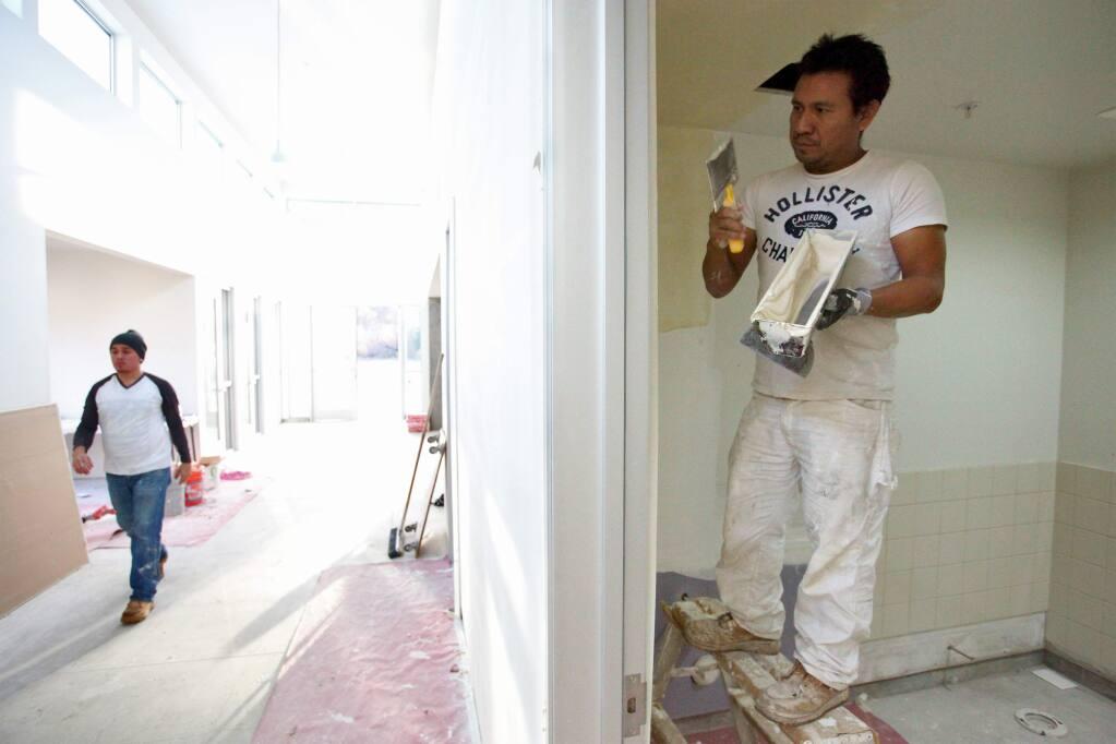 Construction worker Victor Beltran, right, prepares a wall for texturing at the new Sonoma Humane Society Healdsburg Center off Westside Road in Healdsburg on Friday, Dec. 11, 2015. (Alvin Jornada / The Press Democrat)