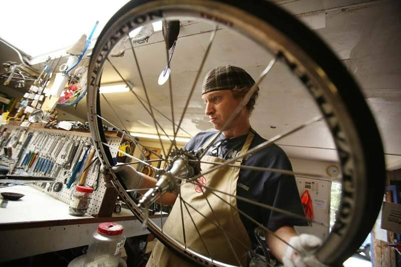 Community Bikes volunteer Michael Garrison fixes a bicycle wheel at their shop off Sebastopol Road in Santa Rosa on Thursday, July 25, 2013. (Conner Jay / The Press Democrat)