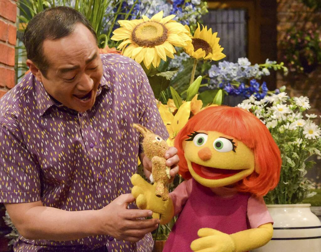 This image released by Sesame Workshop shows castmember Alan Muraoka, left, with Julia, an autistic muppet character debuting on the 47th Season of 'Sesame Street.' The popular children's TV show is celebrating its 50th season. (Zach Hyman/Sesame Workshop via AP)