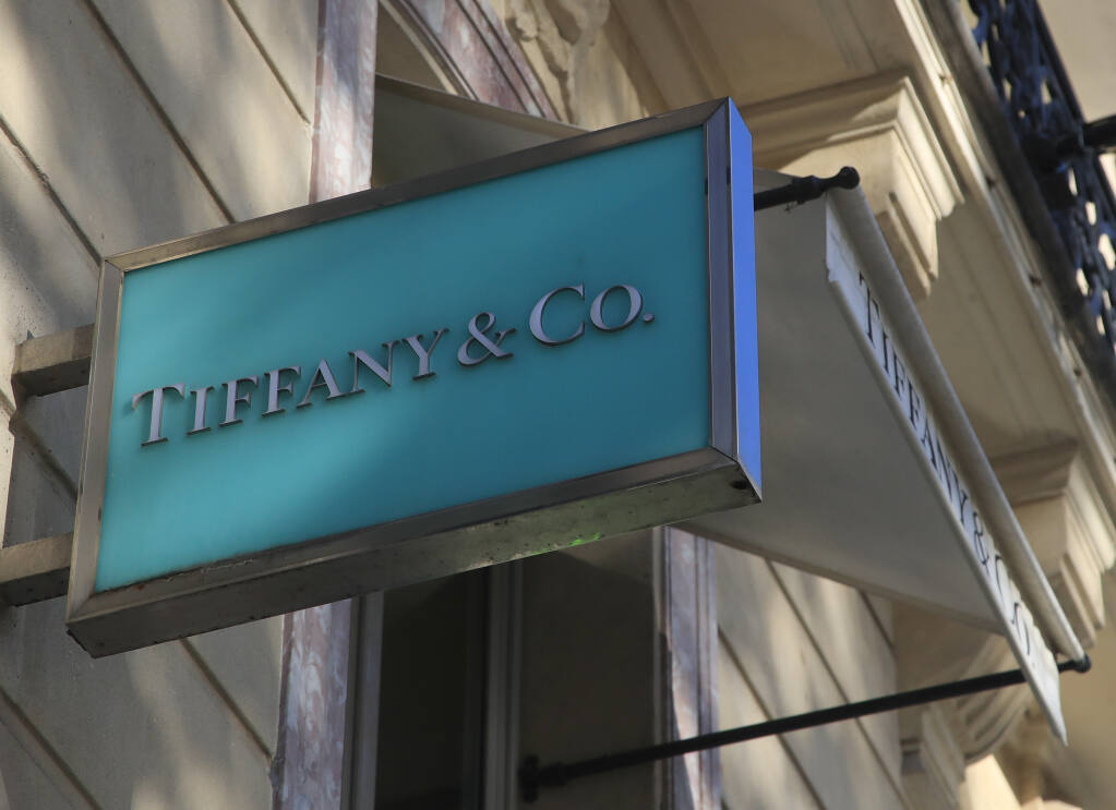 FILE - In this Nov. 25, 2019 file photo, the logo of Tiffany & Co. is pictured on the Champs Elysees avenue in Paris. Luxury goods giant LVMH is ending its takeover deal of the luxury jewelry retailer, citing in part the threat of proposed U.S. tariffs on French goods. (AP Photo/Michel Euler, File)