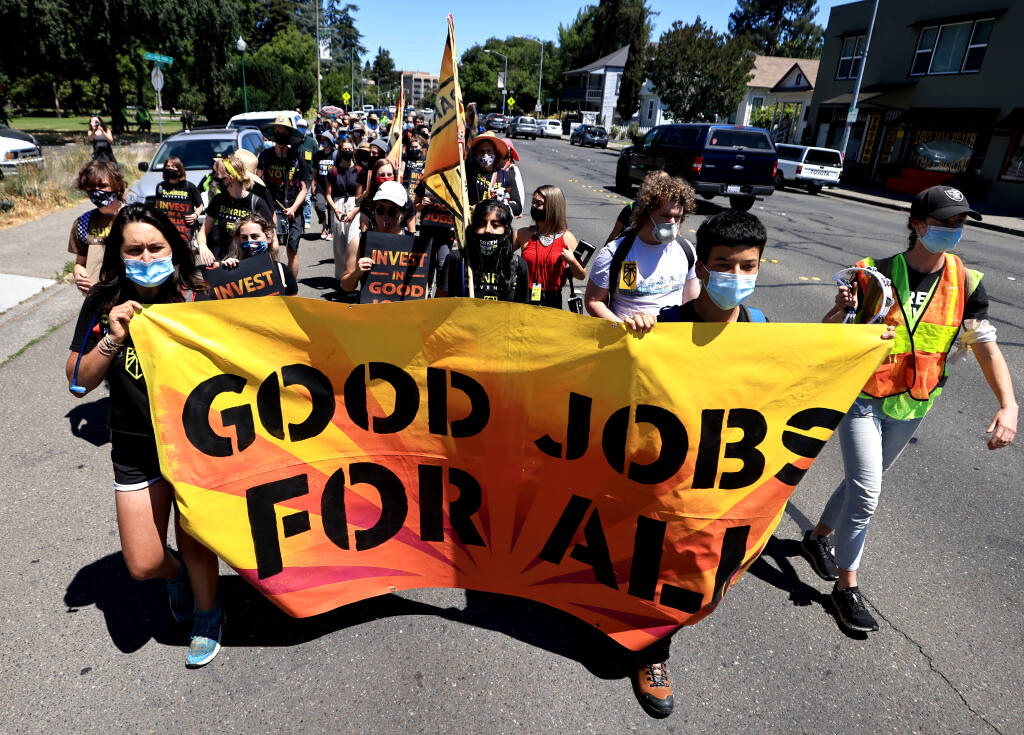 Sunrise Movement activists led by Ema Govea,17, left, of Santa Rosa start the next leg of their walk to complete a 266-mile journey between Paradise and San Francisco, Thursday, June 10, 2021, in Santa Rosa.  (Kent Porter / The Press Democrat) 2021