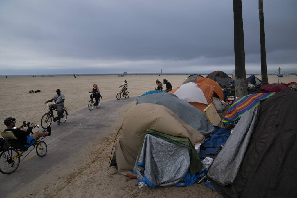 FILE - In this June 29, 2021, file photo people ride their bikes past a homeless encampment set up along the boardwalk in the Venice neighborhood of Los Angeles. The share of Americans living in poverty rose slightly as the COVID pandemic shook the economy last year, but massive relief payments pumped out by Congress eased hardship for many, the Census Bureau reported Tuesday, Sept. 14. The official poverty measure showed an increase of 1 percentage point in 2020, indicating that 11.4% of Americans were living in poverty. It was the first increase in poverty after five consecutive annual declines. (AP Photo/Jae C. Hong, File)