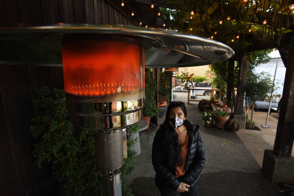 Nicole Penney waiting for guests to arrive next to one of the heaters that help create a comfortable space for outdoor wine tastings at Lambert Bridge Winery in Healdsburg on Friday, Nov. 20, 2020. (Erik Castro / for The Press Democrat)