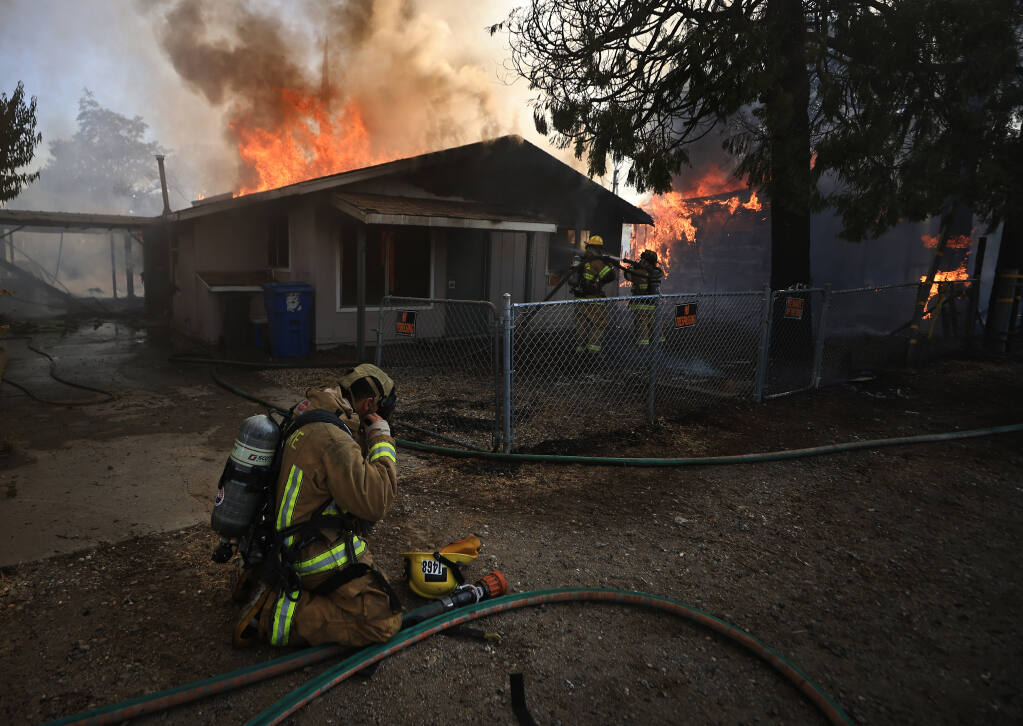 A Cal Fire firefighter puts on an air pack before helping to contain fires that burned five homes in Clearlake Oaks, Sunday, July 18. 2021.  (Kent Porter / The Press Democrat)