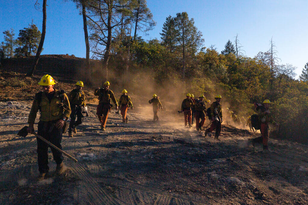 Members of a Cal Fire hand crew file out from a bulldozer line into a ridgeline clearing at Robert Louis Stevenson State Park to prepare for an operation during the Glass fire, near Calistoga, California, on Saturday, Oct. 3, 2020. (Alvin A.H. Jornada / The Press Democrat)