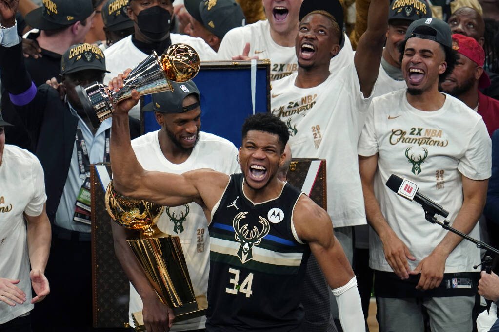 Milwaukee Bucks forward Giannis Antetokounmpo (34) holds with the finals MVP trophy after the Bucks defeated the Phoenix Suns in Game 6 of basketball's NBA Finals in Milwaukee, Tuesday, July 20, 2021. The Bucks won 105-98. (AP Photo/Paul Sancya)