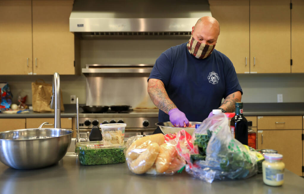 Jacob Mual prepares the meat for his BBQ Pork Meatball Heroes at the Graton Fire Department on Tuesday, March 30, 2021.  (Christopher Chung / The Press Democrat)