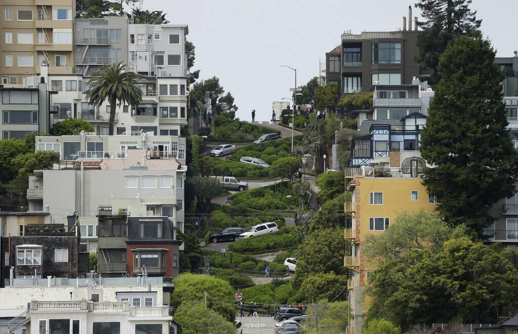 FILE - In this April 15, 2019, file photo, cars wind their way down Lombard Street in San Francisco. (AP Photo/Eric Risberg, File)