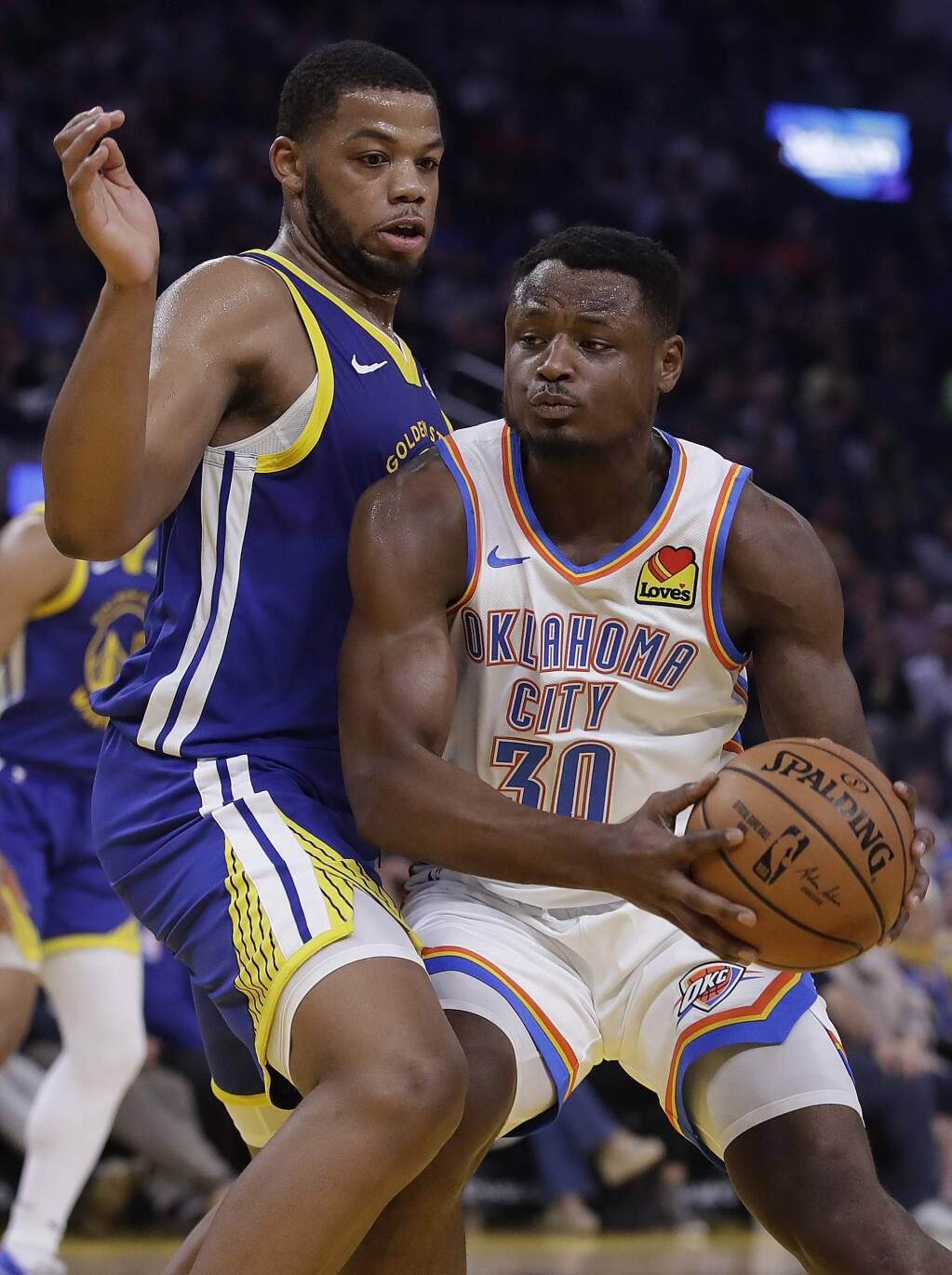 Golden State Warriors' Omari Spellman, left, defends against Oklahoma City Thunder guard Deonte Burton (30) in the first half of an NBA basketball game Monday, Nov. 25, 2019, in San Francisco. (AP Photo/Ben Margot)