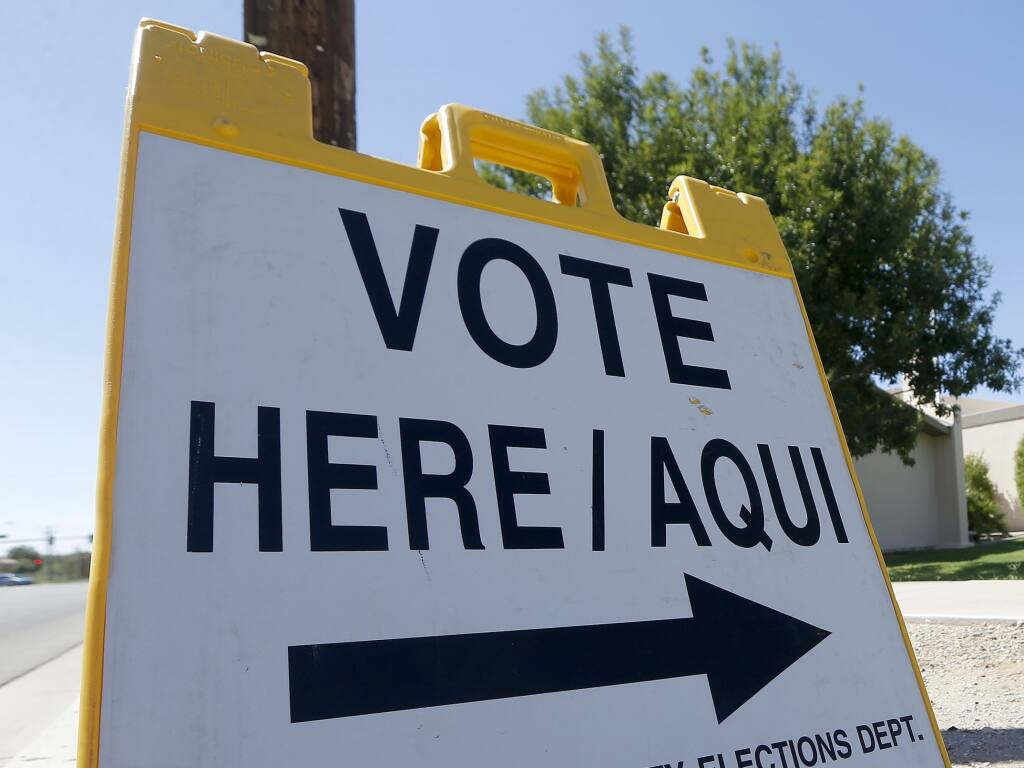 A voting sign directs voters to a precinct on primary election day Tuesday, Aug. 28, 2018, in Phoenix. (AP Photo/Ross D. Franklin)