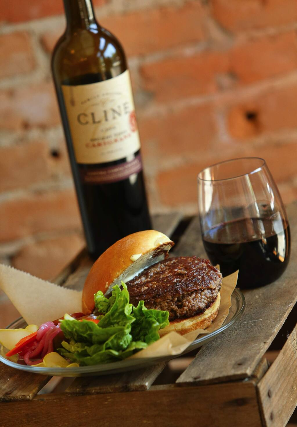 Bacon and grass-fed beef burger created by Travis Day, owner and butcher of Thistle Meats in Petaluma. The burger is paired with Cline Family Cellars 2014 Carignane.(Christopher Chung/ The Press Democrat)