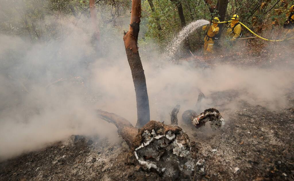 Dry Creek Rancheria firefighters Salvador Lopez, left, and Petro Pulido fight the Kincade fire on a steep hillside at the River Rock Casino in Geyserville on Thursday, October 24, 2019. (Christopher Chung/ The Press Democrat)