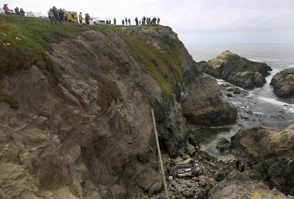 Bodega Bay firefighters work to secure the scene of a crash after a vehicle plummeted from the Bodega Head parking lot, through a wood barrier, landing upside down 100 feet to the rocky shoreline, killing two people in the SUV, Saturday, April 3, 2021. (Kent Porter / The Press Democrat)