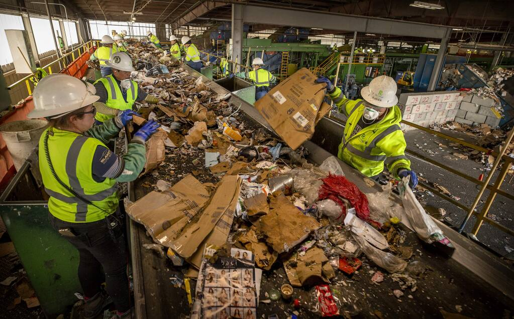 Workers separate cardboard from single stream home recycling cans at Recology Sonoma Marin in Santa Rosa on Monday. The sorters are finding dozens of hypodermic needles daily among the can, bottles and paper goods. (photo by John Burgess/The Press Democrat)