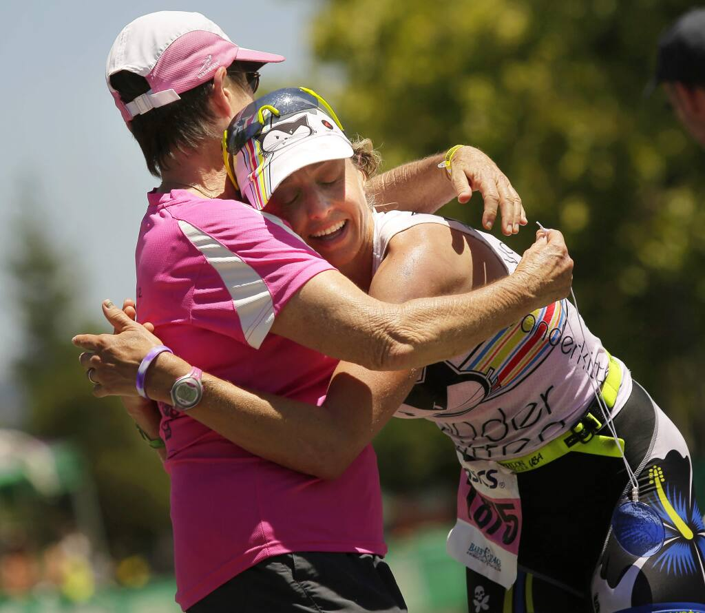 Liza Rachetto hugs Barbara Recchia after finishing first in Barb's Race at the Vineman Triathlon in Windsor on Friday, July 18, 2014. (Conner Jay/The Press Democrat)