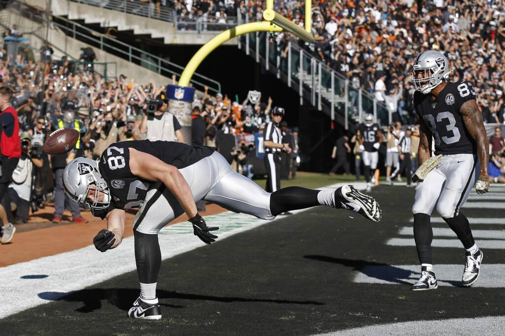 Oakland Raiders tight end Foster Moreau, left, celebrates after scoring a touchdown as tight end Darren Waller looks on during the first half against the Cincinnati Bengals in Oakland, Sunday, Nov. 17, 2019. (AP Photo/D. Ross Cameron)