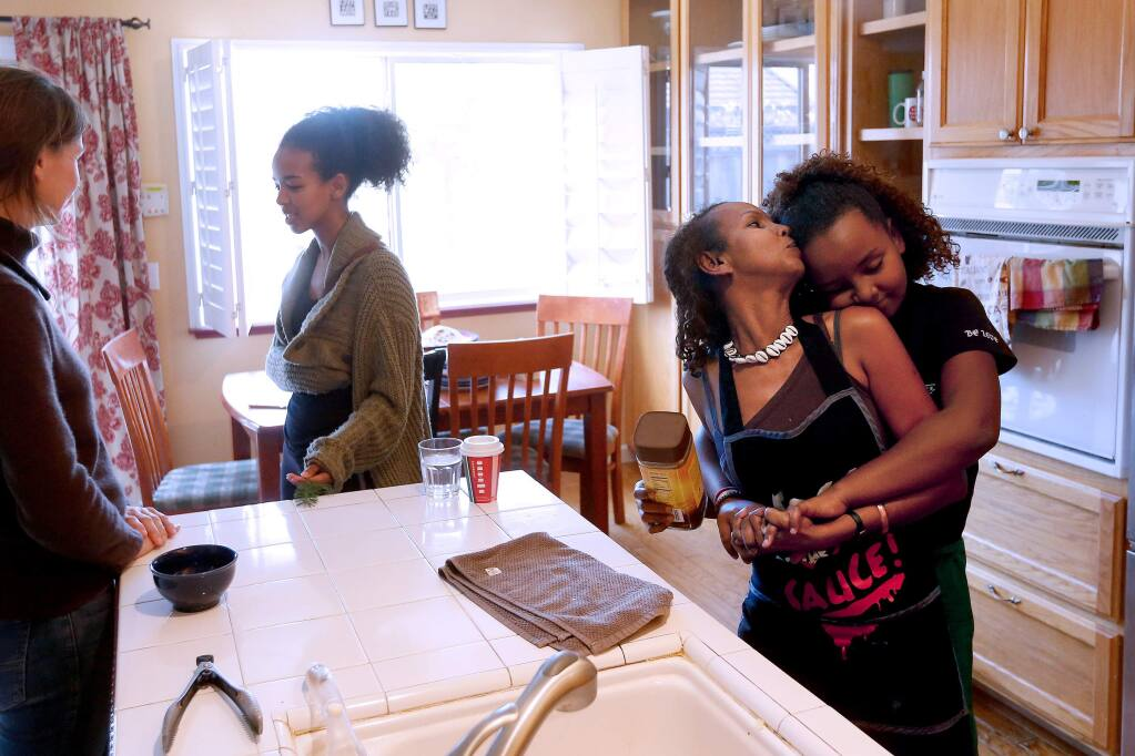 Shugri Salh turns to kiss her daughter Sabina, 11, while they prepare lunch for friends at their home in Rohnert Park, California, on Wednesday, December 26, 2018. (Alvin Jornada / The Press Democrat)