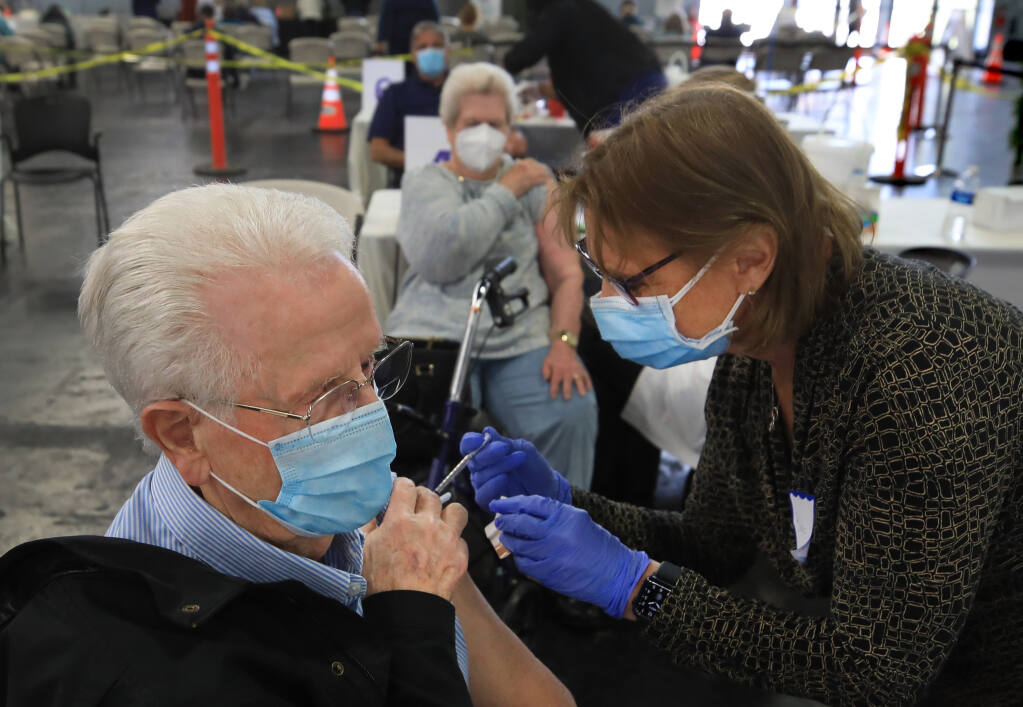 Evan, left, and his wife, Ardath Parry, middle background, receive their second Moderna vaccines, from RN Barbara Kohley, right, and  Dr. Loie Sauer, obscured,  during Sonoma County Medical Association's vaccine clinic at the Sonoma County Fairgrounds, Wednesday, March 3, 2021 in Santa Rosa.  (Kent Porter / The Press Democrat) 2021