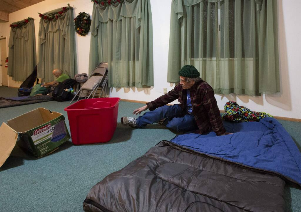 Having made up his bed, John Fassio takes off his shoes before tucking in for the night at the Sonoma Alliance Church on Watmaugh Road. (Photo by Robbi Pengelly/Index-Tribune)