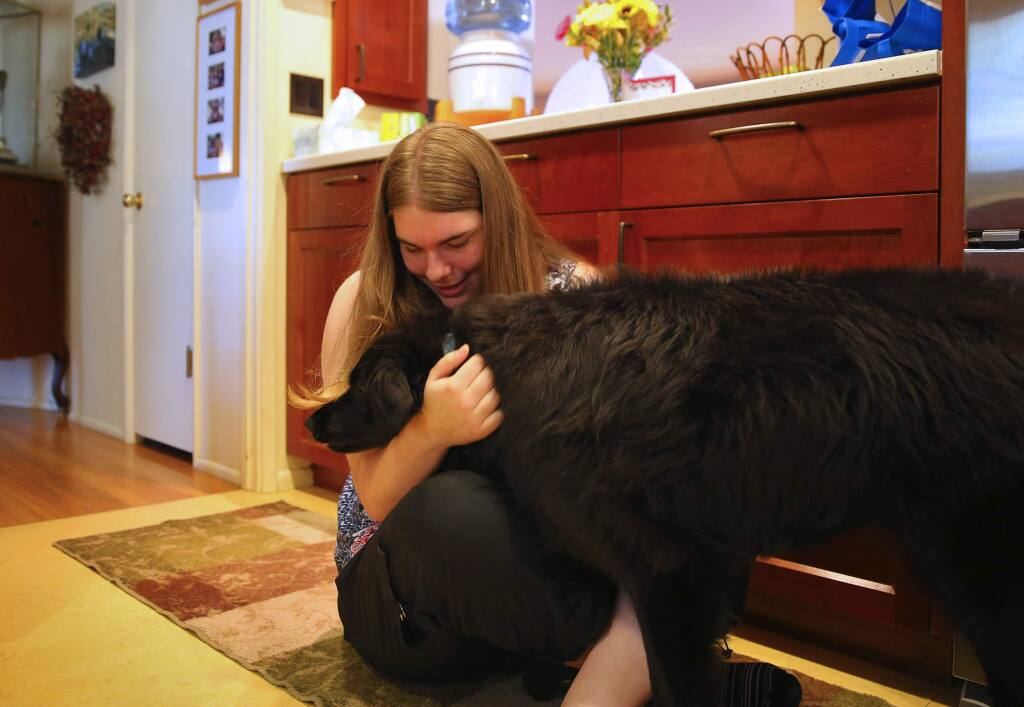 Claire Olney, 17, pets her dog, Bobbi, at her home in Santa Rosa, on Thursday, June 23, 2016. Olney has been diagnosed with Kleine-Levin syndrome, which causes her to sleep for 20 hours per day for a period of approximately six weeks. The episodes occur once or twice per year.(Christopher Chung/ The Press Democrat)