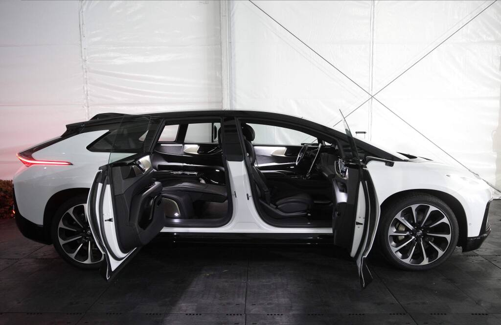 The Faraday Future FF 91, a long, low, and luxurious four-door EV is shown during the 'Faraday's Future: Transforming The Road of Future Mobility,' panel discussion at the AutoMobility LA auto show at the Los Angeles Convention Center in Los Angeles Tuesday, Nov. 19, 2019. (AP Photo/Damian Dovarganes)