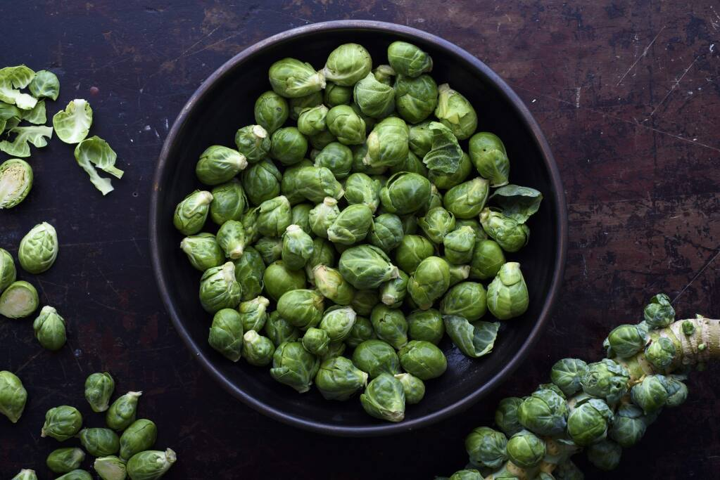 Brussels sprouts on their stalk, lower right, and trimmed in a bowl in New York on Oct. 31, 2016. Brussels sprouts are available year round in cooler climates like coastal California, where most of the nation's supply originates. (Karsten Moran/The New York Times)