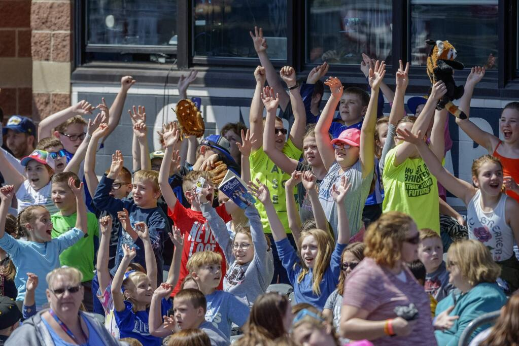 In this April 11, 2018, file photo, schoolchildren cheer as the West Virginia Power face the Lakewood BlueClaws at Appalachian Power Park, in Charleston, W.V. Some towns who have found their minor league teams on a possible Major League Baseball list of 42 teams to eliminate have begun fighting back. (Craig Hudson/Charleston Gazette-Mail via AP, File)