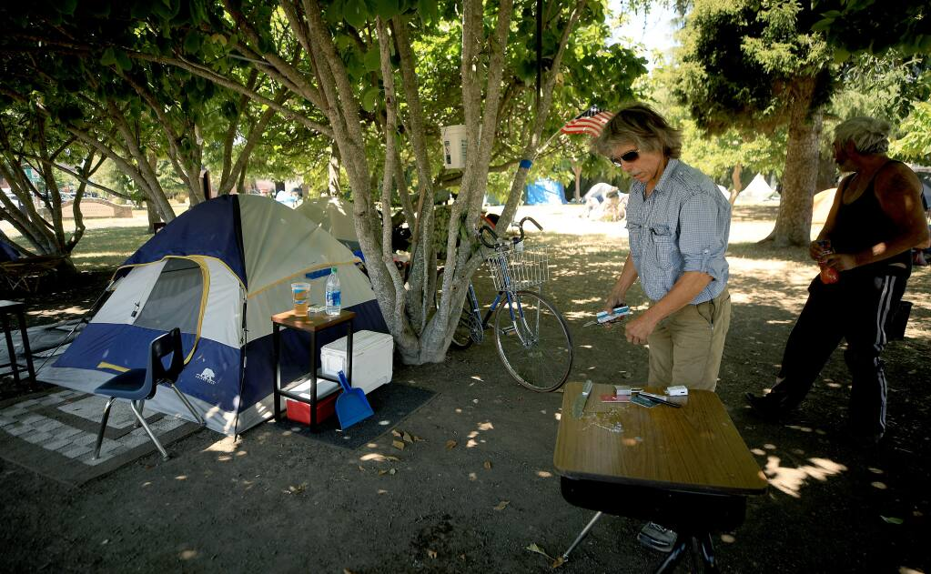James Carver, left, cleans up his campsite in Cancer Survivors Park in downtown Santa Rosa, Tuesday, July 7, 2020.  (Kent Porter / The Press Democrat) 2020