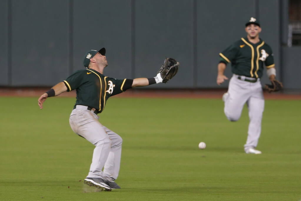Oakland Athletics second baseman Tommy LaStella, left, misses the catch as center fielder Ramon Laureano, right, watches on the hit by Houston Astros' Carlos Correa during the fifth inning of the second baseball game of a doubleheader Saturday, Aug. 29, 2020, in Houston. (AP Photo/Michael Wyke)