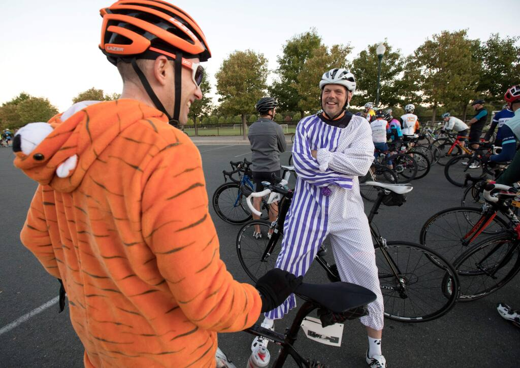 Ryan Kretzer, left, and Paul Reimer, both of Tucson, Arizona, wearing colorful outfits, talk before the start of Levi's GranFondo cycling race, at A Place to Play in Santa Rosa, Calif., on Saturday, October 5, 2019. (Photo by Darryl Bush / For The Press Democrat)