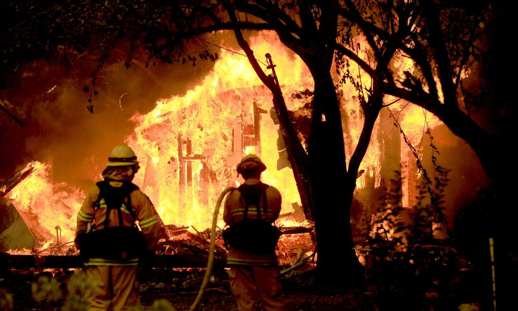 Zac Lewis, left, and Luke Bernardini of the Cloverdale Fire Department keep tabs on a home burning as they protect another structure off Geysers Road due to the Kincade fire that started in the geysers and rolled on to the Alexander Valley floor, Thursday, Oct. 24, 2019. (Kent Porter / The Press Democrat) 2019