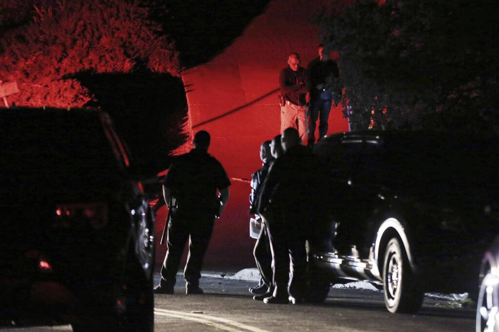 FILE - In this Thursday, Oct. 31, 2019, file photo, Contra Costa County Sheriff deputies investigate a multiple shooting on Halloween at a rental home in Orinda, Calif. Prosecutors said Monday, Nov. 18, 2019, that they won't immediately file criminal charges against five men arrested on suspicion of shooting up a San Francisco Bay Area Halloween party, killing five people. (Ray Chavez/East Bay Times via AP, File)