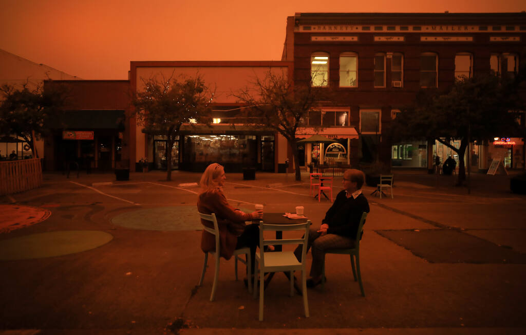 Friends, who requested not to have their names published, share some quiet time on Fourth Street in Santa Rosa, Wednesday, Sept. 9, 2020, as smoke from California wildfires fouls the air. (Kent Porter / The Press Democrat)