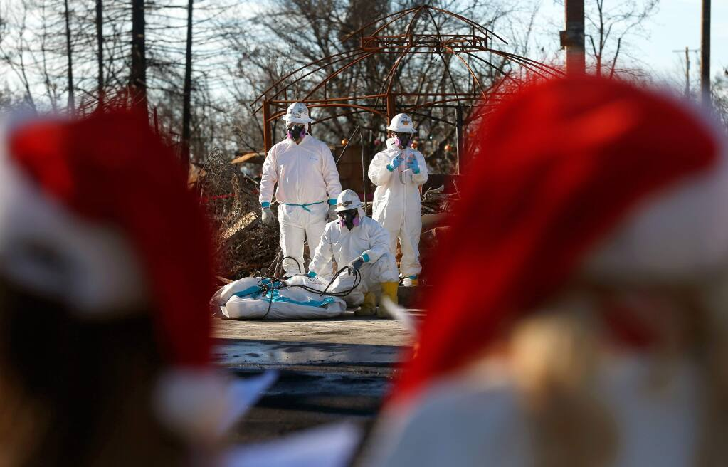 A trio of EPA contractors clad in protective equipment pause their cleanup work at a home on Dogwood Drive to listen as a group of Christmas carolers sings to them, in the Coffey Park neighborhood of Santa Rosa, California on Saturday, December 16, 2017. (Alvin Jornada / The Press Democrat)