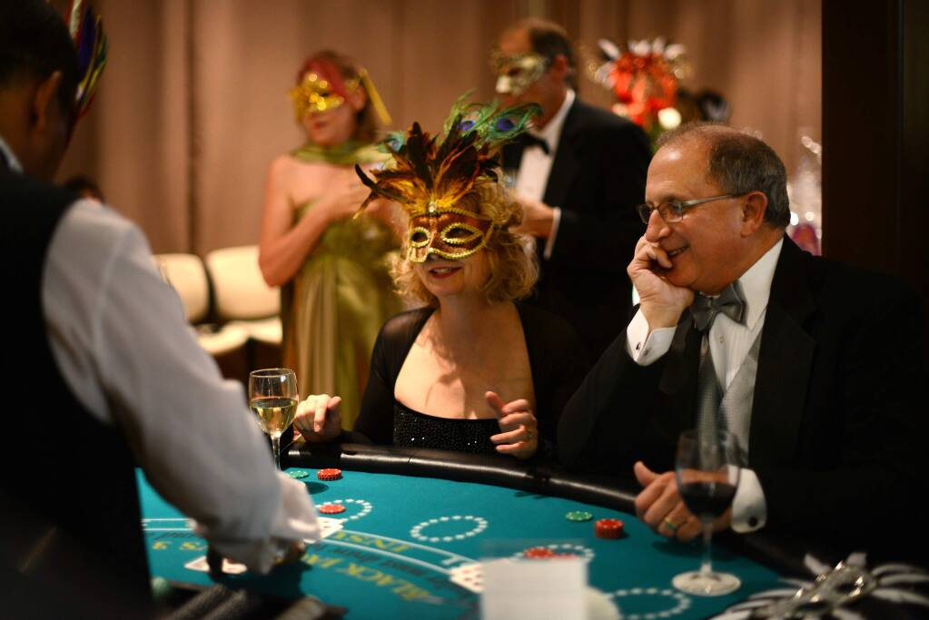 Kim McEachron (left) and John Evans at the blackjack table during the 18th annual 4-A-Child Masquerade Ball, a benefit of the California Parent Institute, held at the DeTurk Round Barn in Santa Rosa on Saturday, Nov. 8, 2014. (ERIK CASTRO/ FOR THE PD)