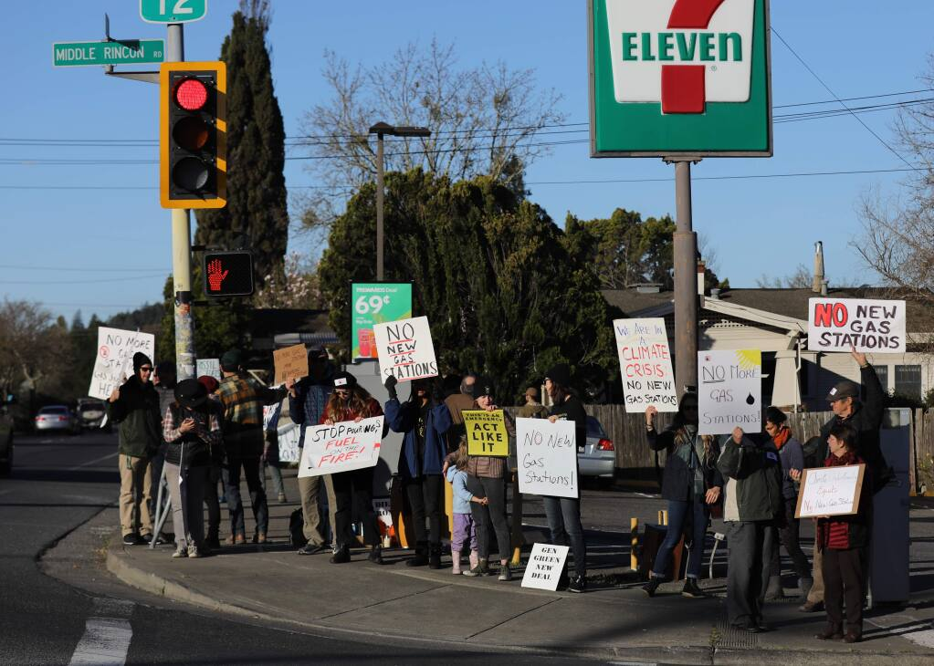 Protesters hold signs in opposition to plans to build a 7-Eleven gas station at the corner of Hwy. 12 and Middle Rincon Rd. in Santa Rosa on Monday, February 24, 2020. (BETH SCHLANKER/ The Press Democrat)