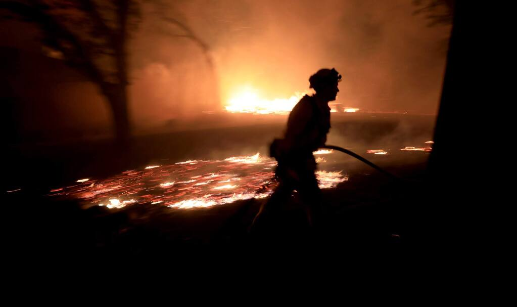 A Cal Fire firefighter races to protect a structure at 1108 Bennett Lane and Highway 128 in Napa County close to the origin of the Tubbs fire, Sunday Oct. 8, 2017. The house later burned to the ground. The home was among the first to catch fire. (Kent Porter / Press Democrat) 2017