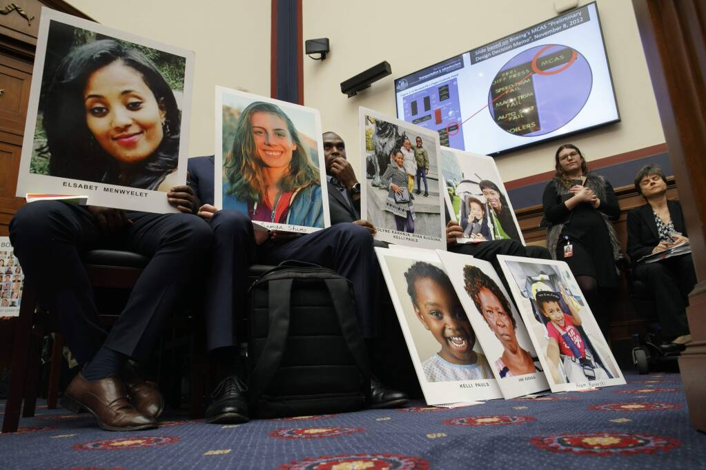 People holding photos of those lost in Ethiopian Airlines Flight 302 and Lion Air Flight 610 listen during a House Transportation and Infrastructure Committee hearing with Boeing executives, Wednesday, Oct. 30, 2019, on Capitol Hill in Washington. (AP Photo/Jacquelyn Martin)