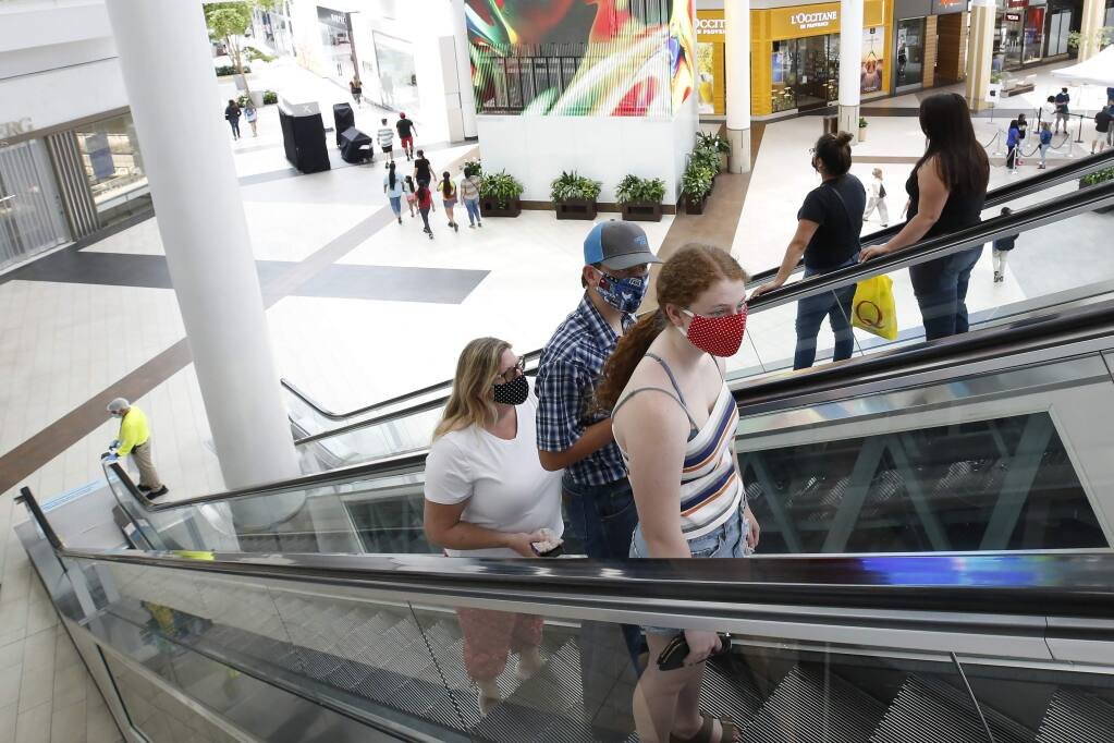 People wearing face masks take an escalator to the second floor of the Arden Fair Mall in Sacramento, Calif., Friday, May 29, 2020. Arden Fair reopened Friday since closing in March due to the coronavirus pandemic. (AP Photo/Rich Pedroncelli)