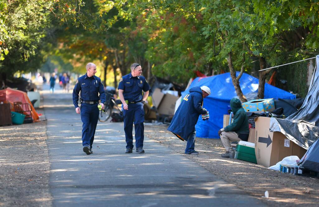 Santa Rosa Fire Department assistant fire marshal Paul Lowenthal, left, and battalion chief Mike McCallum walk through a homeless encampment along the Joe Rodota Trail, west of Stony Point Road, while looking for potential hazards, in Santa Rosa on Monday, October 14, 2019. (Christopher Chung/ The Press Democrat)