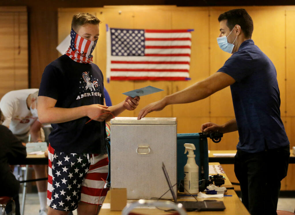Poll supervisor Alex Hachoud, right, shows Tate Jarrell where to drop his ballot at the Rohnert Park Community Center in Rohnert Park, Calif., on Tuesday, September 14, 2021.(Beth Schlanker/The Press Democrat)