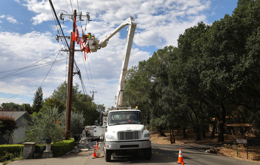 A journeyman linemen from Rokstad, contracted by PG&E, works on moving power lines to a new pole and installs a sectionalizer along Brush Creek Road near Montecito Boulevard in Santa Rosa on Friday, Aug. 14, 2020.  (Christopher Chung / The Press Democrat)
