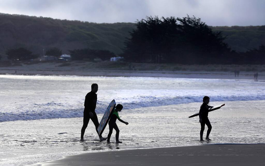 Ian Maxwell heads back into shore with boogie boarders Cael, 6 and Fiona, 8 after the fog rolled in at Doran Beach Regional Park.  (John Burgess / The Press Democrat)