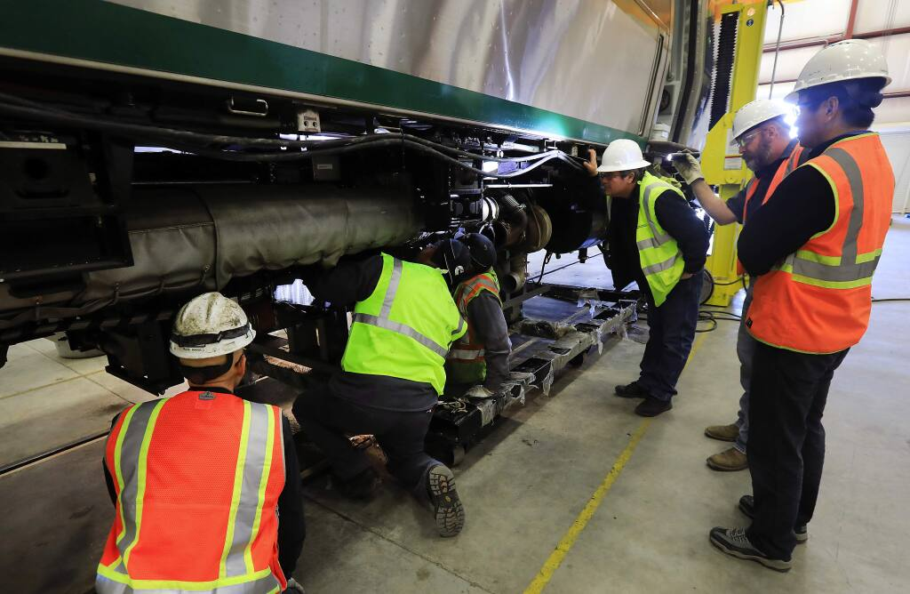 Workers install a rebuilt engine with a new crankshaft into a SMART train at the Rail Operations Center in Santa Rosa on Saturday, December 3, 2016. (John Burgess/The Press Democrat)